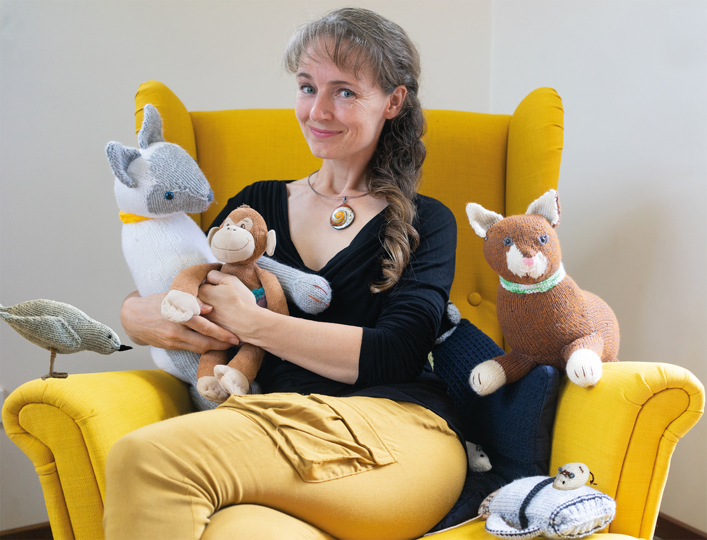 Tina Wilson sitting on a chair with her mother's knitted creations for Monkey's Great Adventures