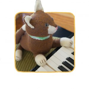 Tomasina the brown knitted cat playing the piano
