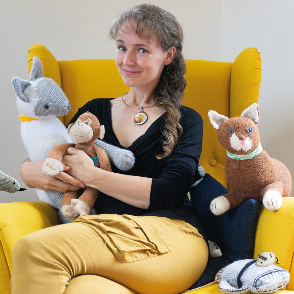 Author/Illustrator Tina Wilson sitting with her mother's knitted creations for the children's picture book series, Monkey's Great Adventures.