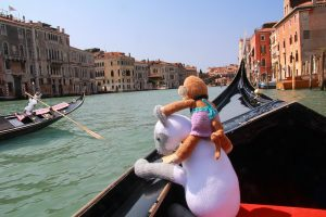Monkey riding a gondola with Clarabella the knitted cat in Venice