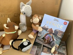 Monkey holding his first children's picture book, Afloat in Venice.